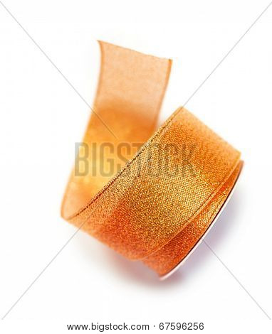 Naturally unwinding coil or reel of orange or amber ribbon. Isolated on white.
