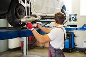 Young serviceman checking wheel alignment  in a car workshop  poster
