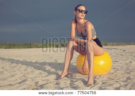 Vintage Styled Model Sitting On Big Yellow Ball At The Beach