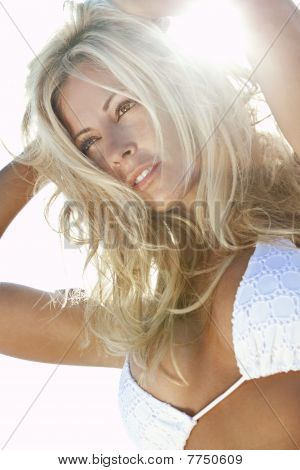 Stunningly beautiful young blond woman in backlit by sunshine and wearing a white bikini poster