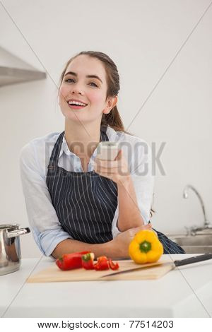 Pretty brunette cooking and watching tv at home in the kitchen