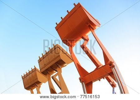 Part of  modern yellow excavator machines,the buckets/shovels raised against blue sky in a construction site.