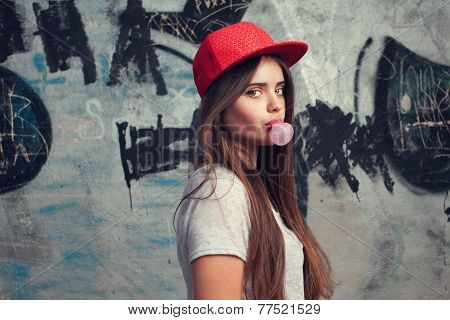Trendy Beautiful Long Haired Yuong Model Posing On Graffiti Background. Blow Bubblegum. Red Cap. Gre