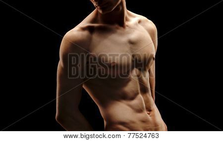 boy with muscular pecs, black background