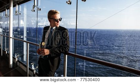 Luxury life. Portrait of the handsome and rich man. Shot from cruise liner. Sea on the background with copyspace poster