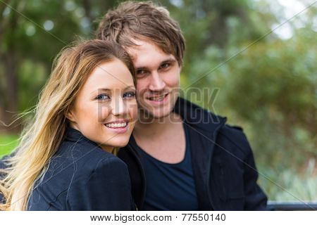 Happy young attractive woman smiling with his handsome boyfriend behind during a romantic time spent in a park