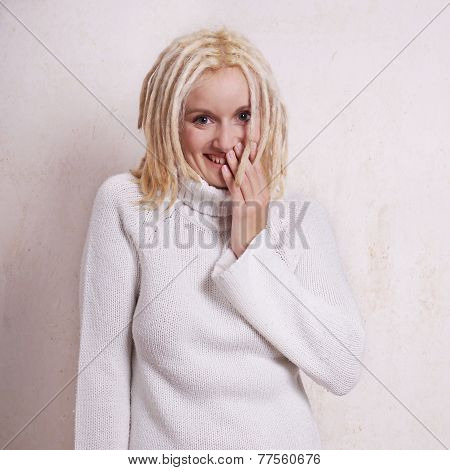 young woman with blonde dreadlocks giggling