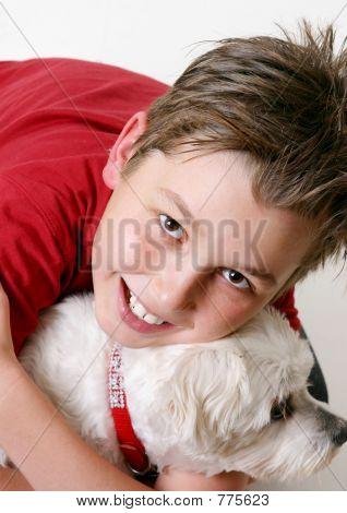 a boy cuddles a pet dog. poster