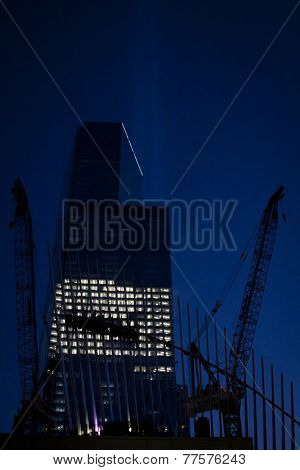 NEW YORK - SEPT 11, 2014: Construction cranes at One World Trade Center, known as the Freedom Tower, at night on the anniversary of the 2001 attacks. The 104-story building opened in November 2014.