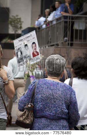 NEW YORK - SEPT 11, 2014: A woman walks up Broadway carrying a sign with pictures of a loved one who perished in the 2001 September 11 terrorist attacks in Lower Manhattan.