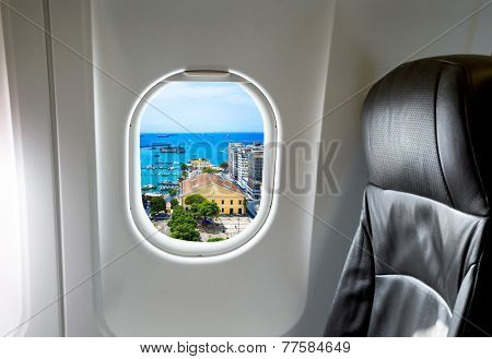 Airplane seat and window inside an aircraft with Salvador city view.