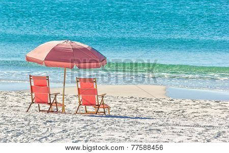 Pink umbrella and lounge chairs on the Miramar Beach in Destin Florida poster