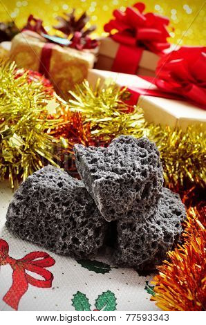 closeup of some lumps of candy coal and some christmas gifts in the background