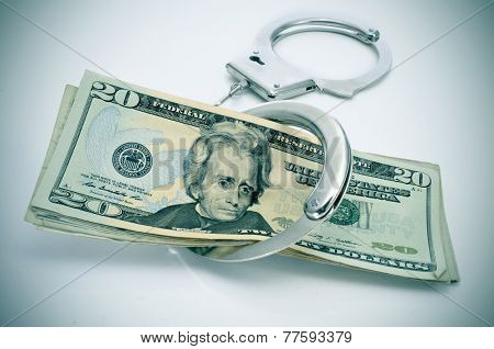 a pair of handcuffs and some dollar bills depicting the idea of arrest for bribery or corruption