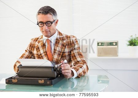 Smiling vintage man using typewriter in his office