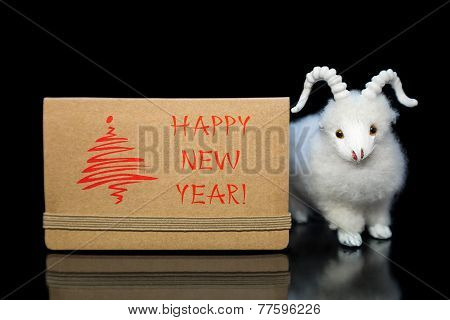 New Year greeting card or postcard with white goat or sheep toy the chinese symbol of 2015 year on black background poster