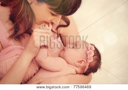 Caring Mother Kissing Little Fingers Of Her Cute Sleeping Baby Girl