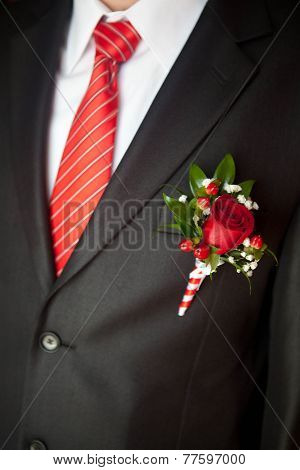 groom's suit close up with a striped tie and buttonhole