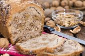 Portion of fresh baked Walnut Bread on dark wooden background poster