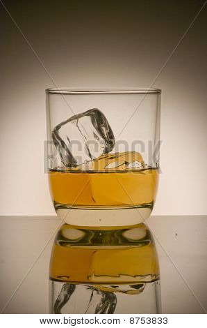 A glass of whiskey on the rocks with ice