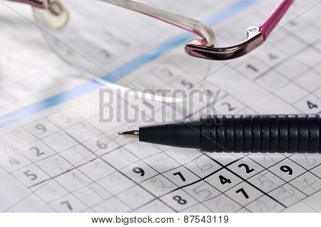 Pencil and glasses lying on a newspaper with a sudoku puzzle