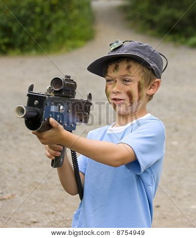 A Young Boy With Camouflage Paint On His Face Preparing To Play War Games