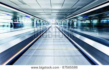 symmetric moving blue escalator inside contemporary airport, hong kong