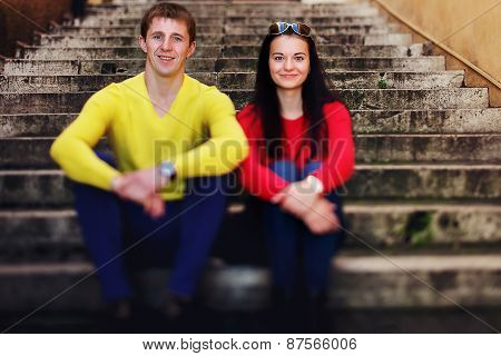 Portrait Of Couple Sitting On Stairs And Kising In Rome