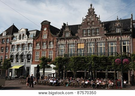 HAARLEM, NETHERLANDS - AUGUST 9, 2012: People sit in a cafe in front of the traditional Dutch houses on the Grote Markt in Haarlem, North Holland, Netherlands.