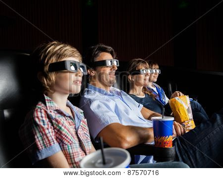 Family with snacks watching 3D movie in cinema theater