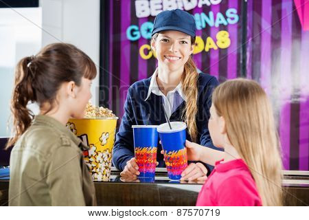Portrait of happy female worker selling snacks to girls at cinema concession stand