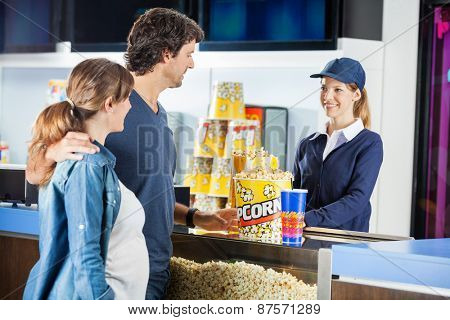 Expectant couple buying popcorn and drink from seller at cinema concession stand poster