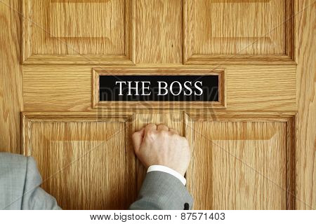 Businessman knocking on a door to