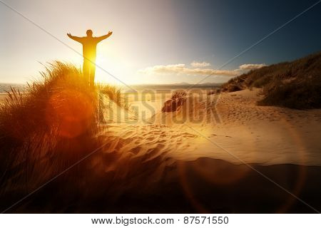 Silhouette of a man with hands raised in the sunset on a beach concept for religion, worship, prayer and praise