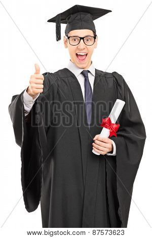 Vertical shot of an overjoyed graduate student in a graduation gown, holding a diploma and giving a thumb up isolated on white background