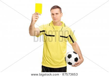 Young male football referee holding a ball and showing a yellow card isolated on white background