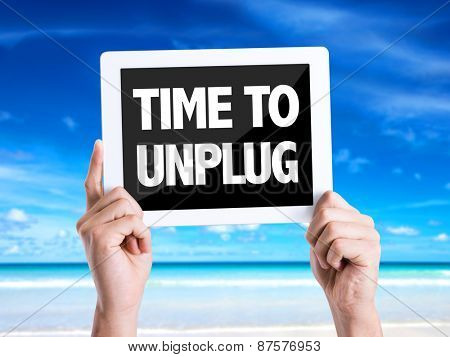Tablet pc with text Time To Unplug with beach background