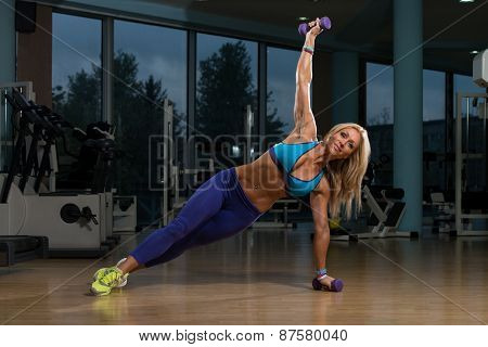 Beautiful Woman Doing Pilates Dumbbell In Fitness Center
