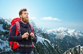 adventure, travel, tourism, hike and people concept - man with red backpack and binocular over alpine mountains background poster