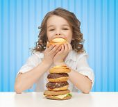 people, nutrition, childhood and health concept - happy little girl eating junk food over blue striped background poster
