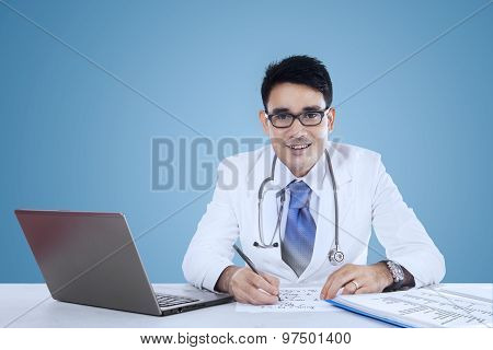 Physician Working On Desk Over Blue Background
