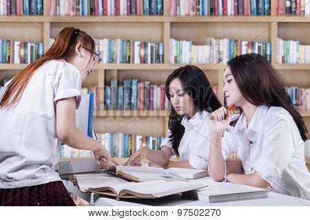 Students Discussing Schoolwork In Library