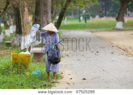 Old woman collects stuff from garbage
