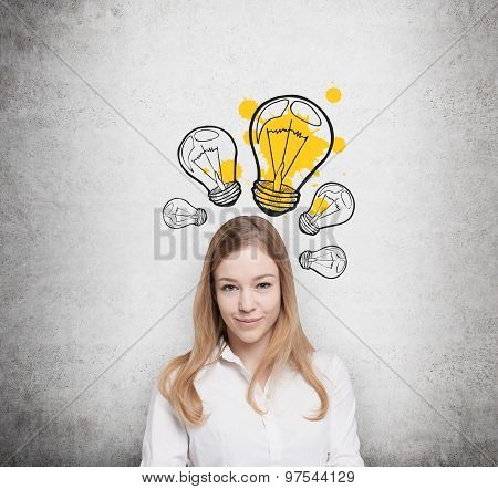 Charming Young Lady Creates New Business Ideas. Drawn Yellow Light Bulbs On The Concrete Wall.