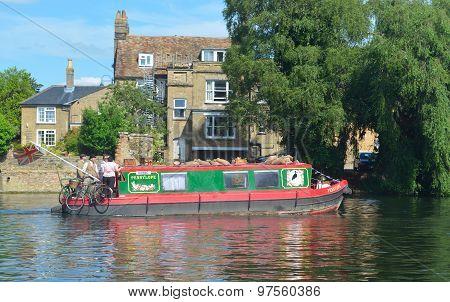 Narrow boat cruising along the river Ouse