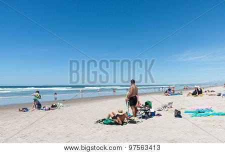 People Enjoying A Summer Day At Beach.