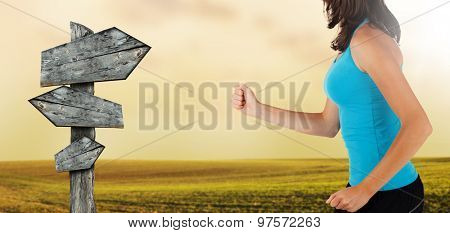 Close-up of woman runner with blank sign post. Detail on body and arms. Concept of body training and healthy lifestyle.