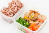 Thai style spicy stir fried shrimps cooked by clean food concept with brown rice and vegetables in lunch box on white table poster