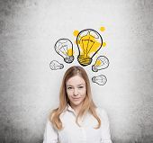 Charming young lady creates new business ideas. Drawn yellow light bulbs on the concrete wall. poster