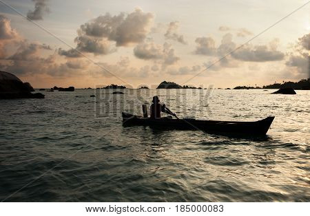 Silhouette Of One Man Rowing A Small Boat With His Paddle On The Ocean At Sunset, Belitung Indonesia